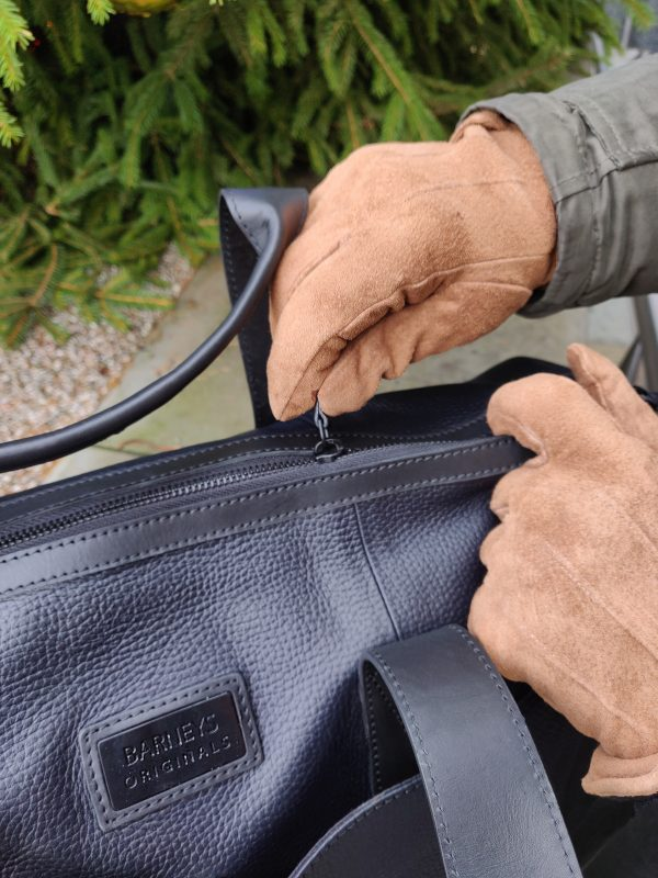 Customer image of real suede tan gloves being used to zip up a bag.