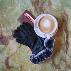 Flat lay shot of unworn real leather gloves with grey faux fur trim on a coffee table, next to a latte and card holder.