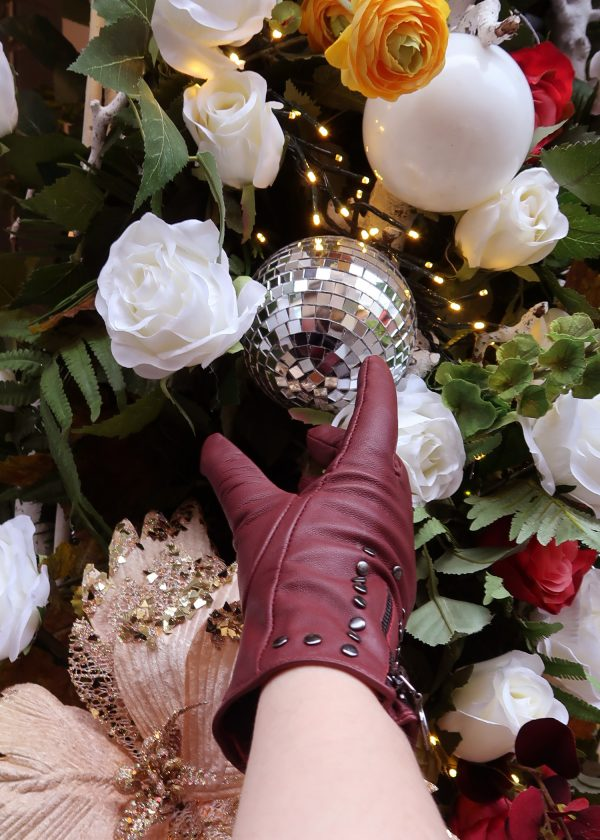A candid shot of our burgundy red studded leather gloves reaching for a floral glitter ball.