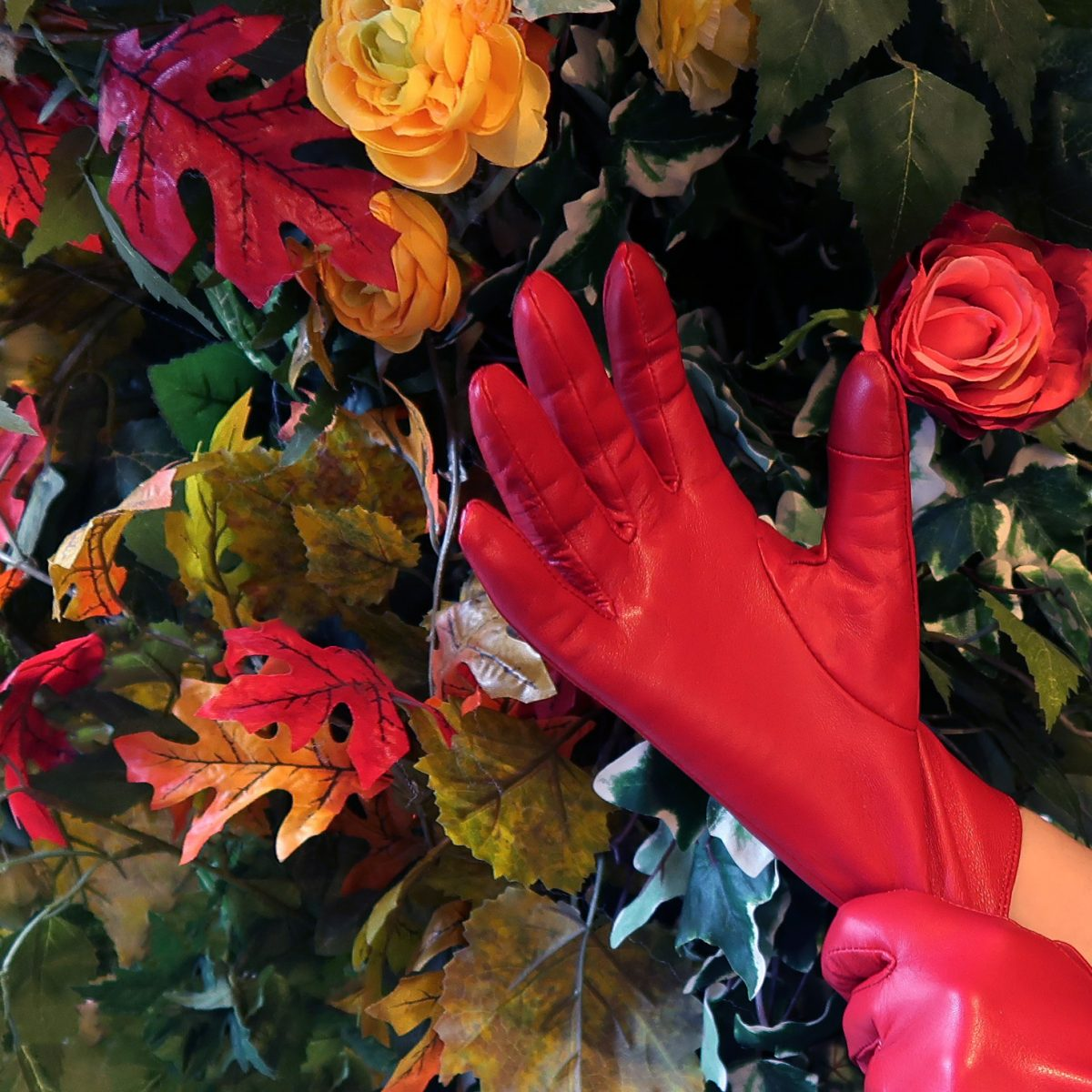 Customer image of the Barneys Originals red leather gloves in front of a floral backdrop.