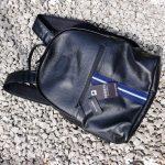 Barneys Originals Backpack bag with blue stripe on gravel.