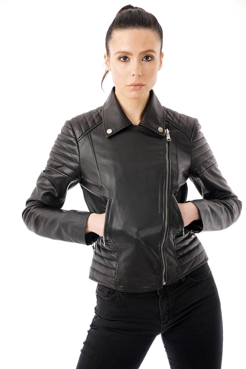 Image displays the 285 real leather biker jacket with shoulder and waist ribbed detailing as worn by our model. She is wearing a size 8. The jacket is zipped up fully to display the asymmetric design. This gorgeous real leather biker jacket also has two pockets which the model is using in the photo. You can also clearly see the pop studs on the lapels.