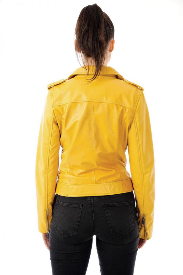 Image displays the yellow biker jacket worn by a size 8 model and shot from behind. You can see the full back design on the jacket. The jacket has a stitched hem that runs across the shoulders to keep the leather panels together. You can also see the waist belt on the bottom hem of the jacket.