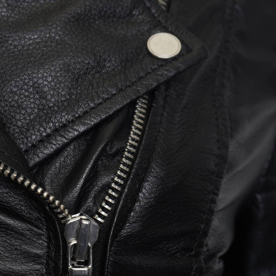 This image shows a Barneys Originals real leather, black, women's, asymmetric jacket with ribbed panelling. This image focuses on the silver zip and collar of the jacket.