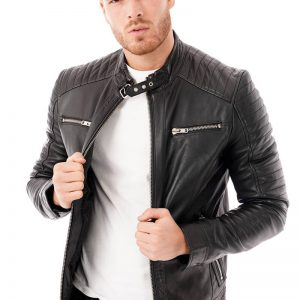 This image shows a Barneys Originals men's black leather jacket with a buckle collar being worn by our model. In this picture he is wearing the jacket open.