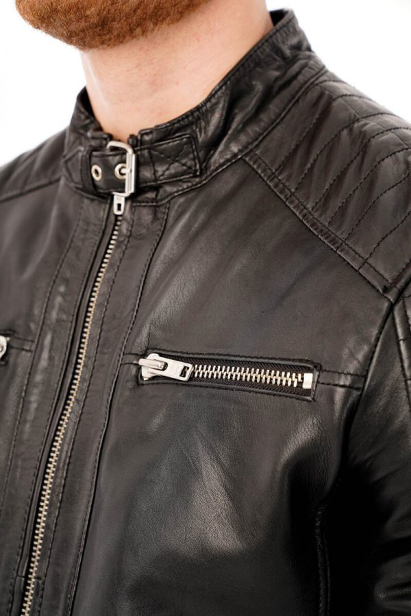 This image shows a Barneys Originals men's black leather jacket with a buckle collar being worn by our model. This picture focuses on the buckle collar and chest of the jacket.