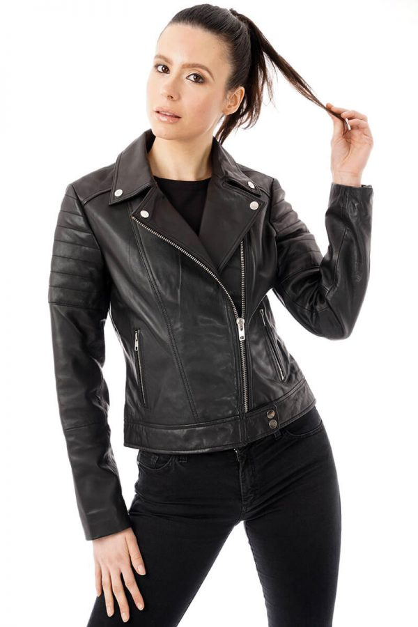 Image shows what the black leather jacket with ribbed shoulders looks like on a size 8 model. Th jacket is zipped halfway to show the silver pop studs on the ends of the lapels.
