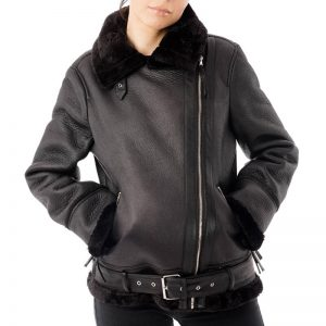 Image displays the faux leather aviator SHR_302 fully zipped up on a size 8 model. The model is posing with her hands in the pockets to demonstrate their use. The jacket features a waistbelt which is also fully enclosed with a buckle on the front of the jacket where the zip begins.