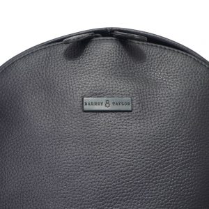 This image shows a black Barney & Taylor backpack. This image focuses on the Barney & Taylor logo.