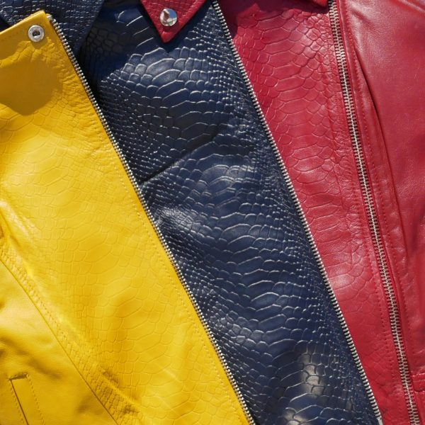 Flat lay shot of the jacket lapel in three different colourways. From left to right the colours are yellow, blue and red. The leather jackets have a subtle croc print embossed texture.