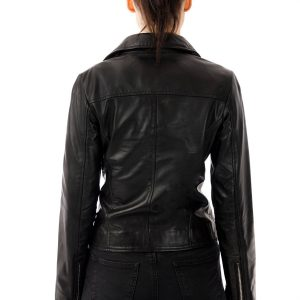 Image displays the Barneys Originals real leather biker jacket for women worn by a model. The image displays the back of the jacket only, where you can see there is no pattern or detail on the back of the item. It is made from smooth, low texture real leather. The back of the sleeves do have zips on the cuffs.
