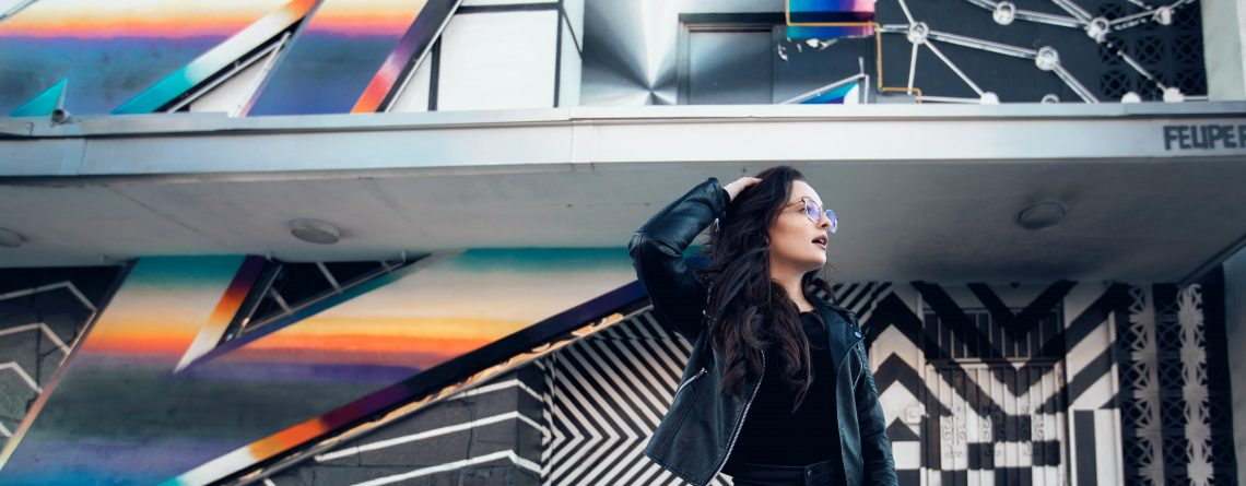 Image displays a woman wearing a leather jacket, black t-shirt and jeans whilst standing in front of a beautiful wall art mural. The mural has a blue and orange stripe across the building and smaller black & white zig zags.