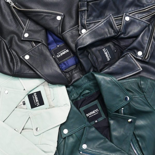 Image displays a flat lay of coloured leather jackets. There is a black leather jacket, blue washed leather jacket, mint green leather jacket and a forest green leather jacket.
