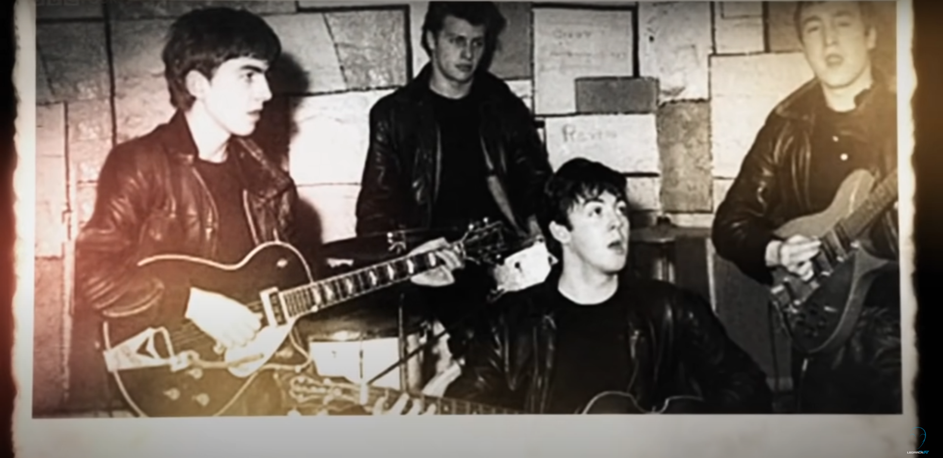 Image shows a classic photograph of The Beatles performing in black leather jackets.