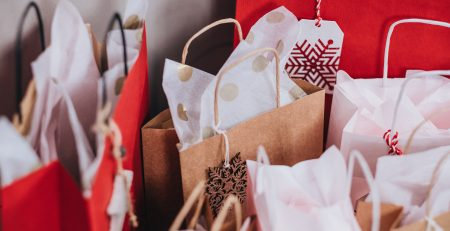Image displays Christmas shopping bags full of gifts wrapped in tissue paper.