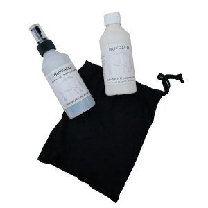 Image displays two bottles sitting on a black draw string bag. The bottles contain a leather cleaner and a leather conditioner.