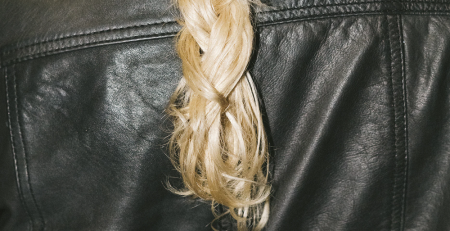 Image displayed shows blonde hair drapped over the back of a leather jacket.