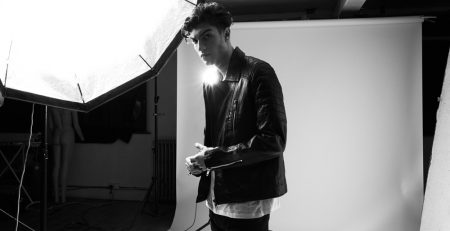 Image displays a man wearing a leather jacket under studio lights. the jacket has quilted shoulders and is a classic asymmetric fit. The image is shot in black and white.