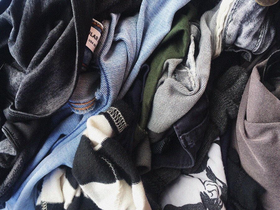 Image displays a pile of clothes that have been worn and tossed away.