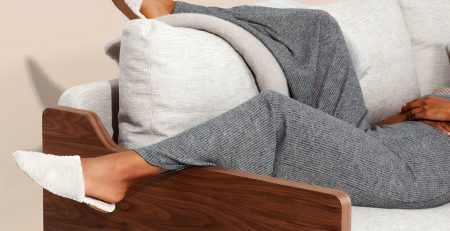 Image displays the legs of a person lazily draped over the arm of a sofa, they are wearing a grey lougewear set with white slippers.