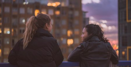 Image displays two friends looking out onto a city skyline. One is wearing a leather jacket, the other is wearing a padded coat.