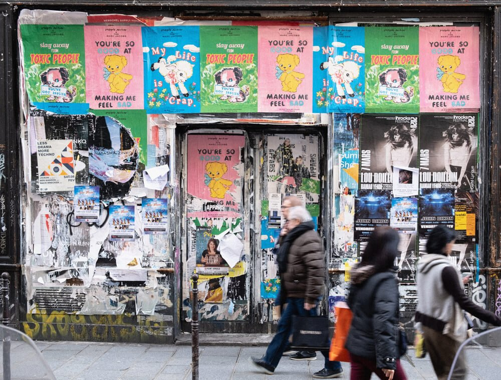 Image description: People walk past authentic advertising posters on a busy street. The posters are bright with cartoon characters talking about how advertising makes them feel bad.