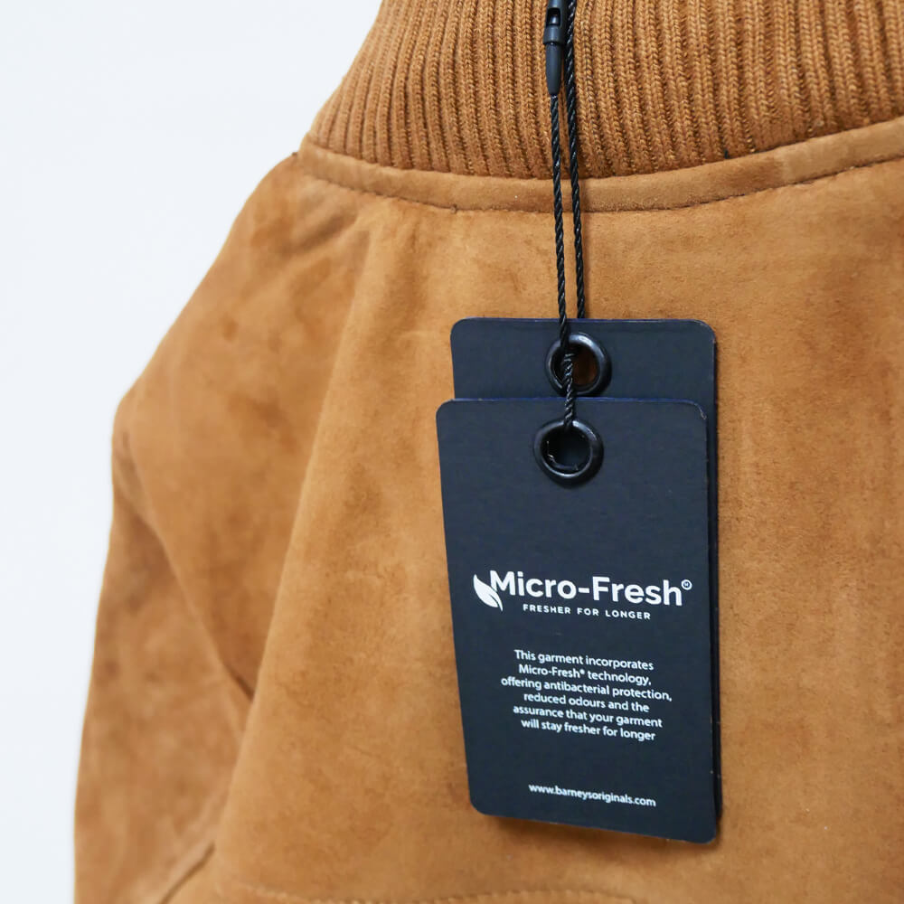 This image displays the tan suede jacket up close to zoom in on a tag which says: 'Micro-Fresh: Fresher for longer' This garmnent features micro-fresh technology offering anti bacterial protection.